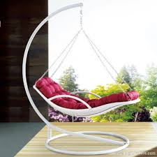 furniture white swingasan chair with red cushion on wooden floor