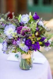 purple and blue flowers arrangement with elegant vase glass