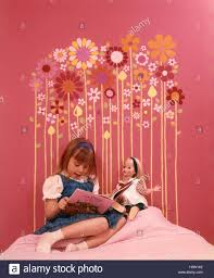 1970s girl sitting bed reading to doll pink walls bedroom 1970s girl sitting bed reading to doll pink walls bedroom headboard made of colorful flower shapes glued to wall