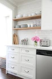 Kitchens With White Cabinets And Black Countertops by Black And White Kitchen Features White Shaker Cabinets Accented