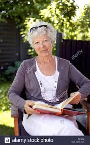 Chair In Garden Happy Mature Woman Sitting On A Chair In Garden With A Book