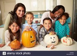 mothers and children making halloween lanterns stock photo