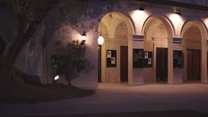 wedding arches with lights dusk 2 story live theater white brick tiled roof arches