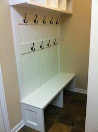 vintage white beadboard mudroom bench using iron coat hook and