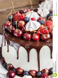 cake decorated with chocolate meringues and fresh berries stock