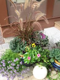 fall planter with ornamental grass pansies veggies kale