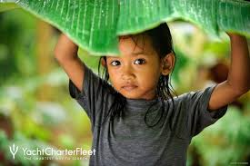 Cute small girl protecting from rain by the leaf  Indonesia Photo Tour