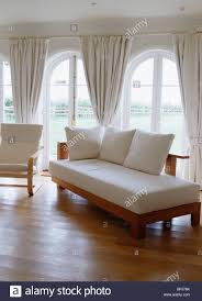 day bed with white cushions in living room with wooden floor and