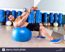 dumbbell bench press on fit ball man workout at fitness gym stock