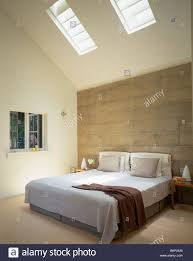 Modern White Bed Frames Concrete Wall Behind Bed With White Bed Cover And Gray Cushions In