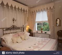 gothic style canopy and drapes above brass bed in townhouse