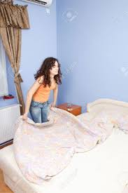 a teen happily making her bed in her room stock photo
