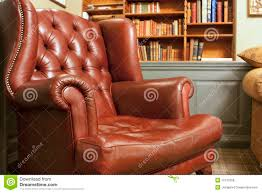 old style armchair in front of bookshelves royalty free stock