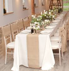 indoor long wedding dining table with white flower centerpieces