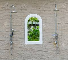 Outdoor Pool Showers - outdoor shower with sand stone background at swimming pool stock