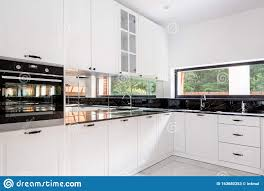white kitchen cupboards with black granite tops luxury kitchen interior in black and white stock image