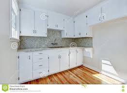 white kitchen cabinets with light tone hardwood floor stock photo