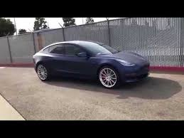 tesla model 3 with amazing matte blue wrap large custom rims and