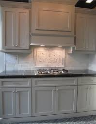 kitchen with gray painted cabinets marble backsplash and black