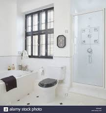 black plantation shutters above bath and black toilet seat in