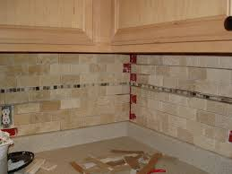 travertine subway tile kitchen backsplash with a mosaic glass