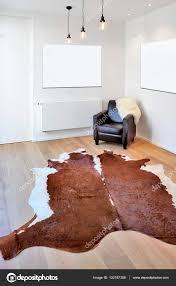 tappeto di mucca tappeto di mucca e poltrona il nuovo pavimento in legno foto