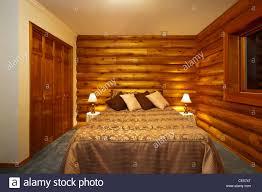 bedroom in luxury log cabin featuring cedar logs and rustic trim
