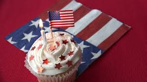 two patriotic birthday cupcakes with burning candles and tiny