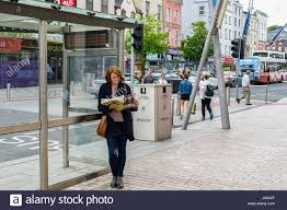 woman reading magazine by bus stop in cork ireland with copy
