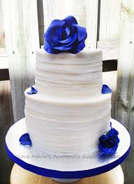 textured buttercream cake with royal blue roses and petals