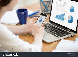 home design app for laptop businesswoman holding smartphone while working laptop stock photo