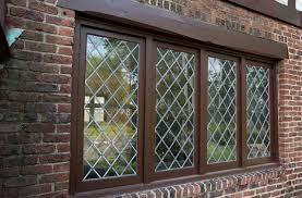 tudor style windows with dark brown windows frame and red brick