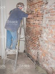 Exposed Brick Wall by House Renovationsenior Man Scraping An Exposed Brick Wall Stock