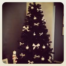 black christmas tree with white and silver bows and ornaments