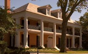 greek revival style house front colonnade with front porch and deck balcony of a greek