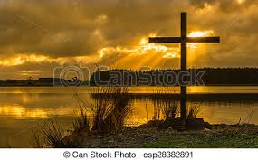 sunrays cross black cross by a lake with sun rays shining
