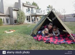 father and daughters using digital tablet in backyard tent stock