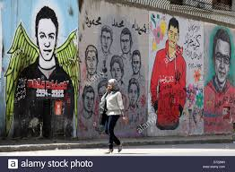 woman walks in front of a revolutionary mural on a wall of martyrs stock photo woman walks in front of a revolutionary mural on a wall of martyrs near tahrir square in cairo