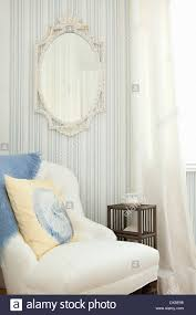 mirror on striped wall above armchair in blue and white bedroom
