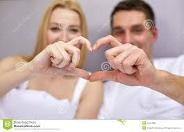 smiling couple in bed making heart shape gesture stock photo