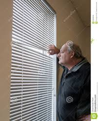 older man looking out window blinds royalty free stock photos