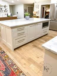 white kitchen cabinets with oak floors carrara marble countertops marble countertop island revere