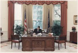file photograph of president reagan working at his desk in the