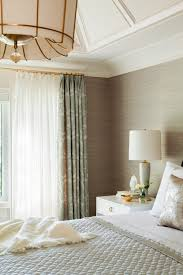 grasscloth wallpaper brass curtain rods statement chandelier textured wallpaper it neutral bedroom via jennifer worts design
