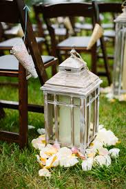 aisle markers vintage style lanterns with candles and flower petals as aisle