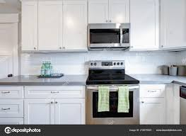 white kitchen cabinets with stainless steel backsplash white and gray kitchen room with modern stainless steel appliances quartz countertops and subway tile backsplash 216878920
