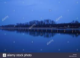 beautiful reflection of the trees and lights in the lake ada stock