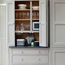 grey bi fold kitchen cupboard doors reveal wooden shelving inside