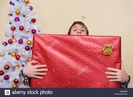 young man holding large wrapped gift box decorated white christmas