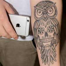 forearm tattoo of an owl with a sugar skull on the belly men